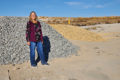 Rebecca Webb standing in front of the rock being used for landscaping at the IGSFMM site.