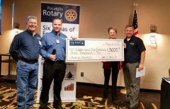 Richie Evans presenting the DL Evans Bank sponsorship check at a Pocatello Rotary Club meeting.